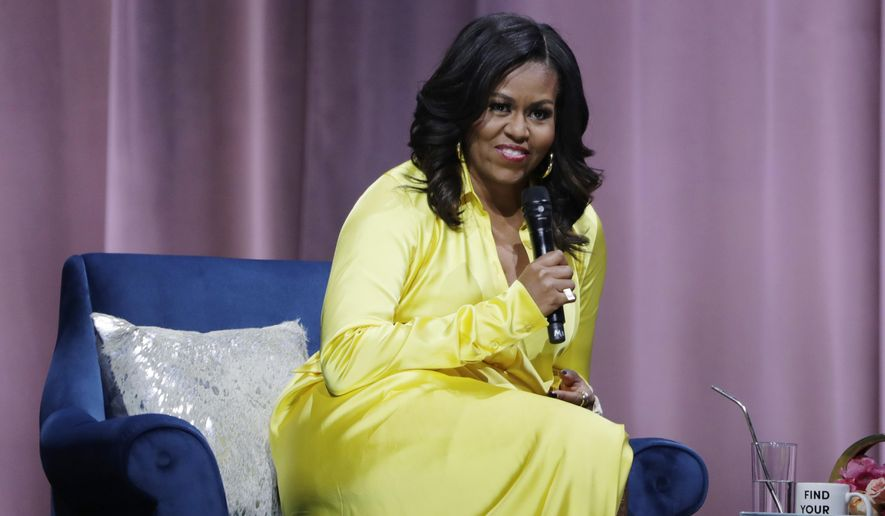"Former first lady Michelle Obama responds to questions as she is interviewed by actress Sarah Jessica Parker during an appearance for her book, ""Becoming: An Intimate Conversation with Michelle Obama"" at Barclays Center Wednesday, Dec. 19, 2018, in New York. (AP Photo/Frank Franklin II)"