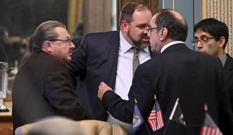 """From left, senators Mike Kowal, R-White Lake, and Jim Annanich, D-Flint, talk with staff about an amendment to be considered as the Michigan senate takes on a flurry of bills on what should be the last day of the """"lame duck"""" session, Thursday, Dec. 20, 2018. (Dale G. Young/Detroit News via AP)"""