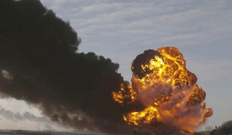 FILE - In this Dec. 30, 2013 file photo, a fireball goes up at the site of an oil train derailment near Casselton, N.D. The Trump administration vastly understated the potential benefits of installing more advanced brakes on trains that haul explosive fuels when it cancelled a requirement for railroads to begin using the equipment. A government analysis used by the administration to justify the cancellation omitted up to $117 million in potential reduced damages from using electronic brakes. Department of Transportation officials acknowledged the error after it was discovered by The Associated Press during a review of federal documents but said it would not have changed their decision. (AP Photo/Bruce Crummy, File)