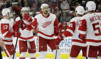 Detroit Red Wings' Jonathan Ericsson, center facing, of Sweden, celebrates his goal against the Carolina Hurricanes with teammates during the third period of an NHL hockey game in Raleigh, N.C., Thursday, Dec. 20, 2018. Detroit won 4-1. (AP Photo/Gerry Broome)