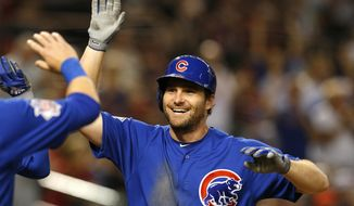 FILE - In this Sept. 18, 2018, file photo, Chicago Cubs second baseman Daniel Murphy is congratulated during the team's baseball game against the Arizona Diamondbacks in Phoenix. The Colorado Rockies have brought in Murphy to boost an offense big on pop but lackluster in batting average. The veteran infielder has agreed to a $24 million, two-year contract with the Rockies, a person familiar with the negotiations told The Associated Press on Thursday night, Dec. 20. The person spoke on condition of anonymity because the deal was subject to a successful physical. (AP Photo/Rick Scuteri, File) **FILE**