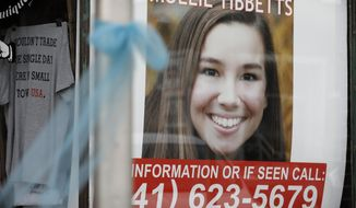 FILE - In this Aug. 21, 2018, file photo, a poster for missing University of Iowa student Mollie Tibbetts hangs in the window of a local business in Brooklyn, Iowa. (AP Photo/Charlie Neibergall, File)