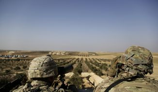 American troops look out toward the border with Turkey from a small outpost near the town of Manbij, northern Syria. (AP Photo/Susannah George, File)
