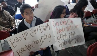 Bill Nguyen, 12, and Jade Nguyen, 9, hold signs at a rally protesting President Donald Trump's deportation policy to deport Vietnamese refugees, at the Mary Queen of Vietnam Church in New Orleans, Thursday, Dec. 20, 2018. (AP Photo/Gerald Herbert)