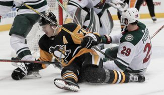 Pittsburgh Penguins' Evgeni Malkin (71) and Minnesota Wild's Greg Pateryn (29) hit the ice during the second period of an NHL hockey game Thursday, Dec. 20, 2018, in Pittsburgh. (AP Photo/Keith Srakocic)