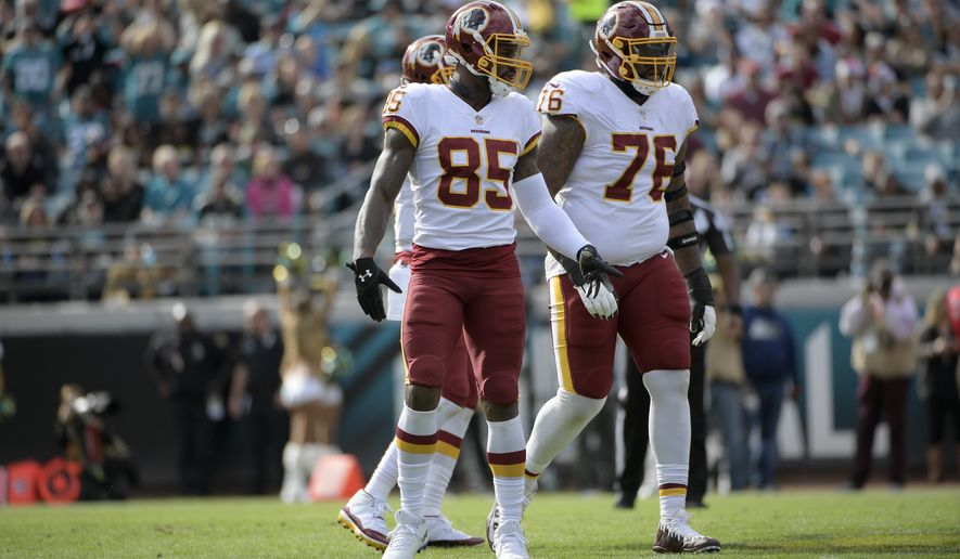 Washington Redskins tight end Vernon Davis (85) and offensive tackle Morgan Moses (76) set up for a play during the first half of an NFL football game against the Jacksonville Jaguars Sunday, Dec. 16, 2018, in Jacksonville, Fla. (AP Photo/Phelan M. Ebenhack)