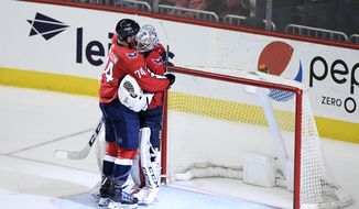 Washington Capitals defenseman John Carlson (74) hugs goaltender Braden Holtby (70) after an NHL hockey game against the Buffalo Sabres, Friday, Dec. 21, 2018, in Washington. (AP Photo/Nick Wass) ** FILE **