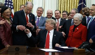 President Donald Trump hands a pen to Sen Chuck Grassley, R-Iowa, after signing criminal justice reform legislation in the Oval Office of the White House, Friday, Dec. 21, 2018, in Washington. Rep. Virginia Foxx, R-N.C, front row, second from right, watches. (AP Photo/Evan Vucci) **FILE**