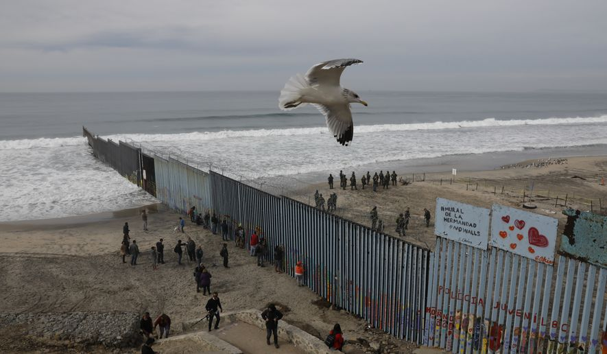 In this Dec. 10, 2018, file photo, people look on from the Mexican side, left, as U.S. Border Patrol agents on the other side of the U.S. border wall in San Diego prepare for the arrival of hundreds of pro-migration protestors, seen from Tijuana, Mexico. A relentless stream of U.S. policy shifts in 2018 has amounted to one of the boldest attacks on all types of immigration that the country has ever seen. Some see it as a tug-of-war between foundational national ideals and a fight for a new path forward led by President Donald Trump. (AP Photo/Rebecca Blackwell) **FILE**