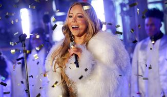 """FILE - In this Dec. 31, 2017 file photo, Mariah Carey performs at the New Year's Eve celebration in Times Square in New York. A poll shows more Americans are favoring Christmas carols over recent Billboard hits, while longtime classics and recent comedies are the most preferred to watch during the holiday season. A poll by The Associated Press-NORC Center for Public Affairs Research shows """"Silent Night"""" as the country's most popular, despite Mariah Carey's """"All I Want for Christmas Is You"""" becoming the highest-charting Billboard Hot 100 holiday hit in 60 years. (Photo by Brent N. Clarke/Invision/AP, File)"""