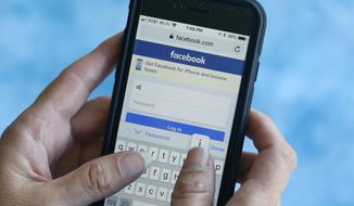 In this Aug. 21, 2018 file photo, a Facebook start page is shown on a smartphone in Surfside, Fla. (AP Photo/Wilfredo Lee, File) **FILE**