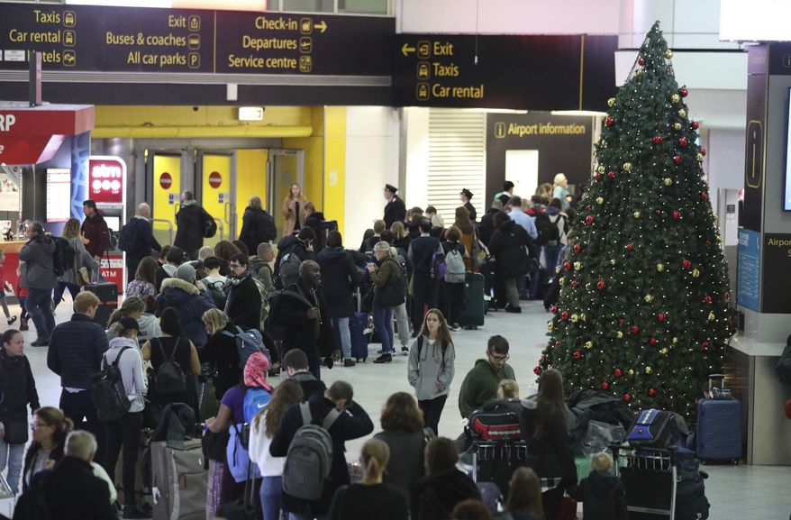 Passengers at Gatwick airport wait for their flights following the delays and cancellations brought on by drone sightings near the airfield, in London, Friday Dec. 21, 2018. New drone sightings Friday caused fresh chaos for holiday travelers at London's Gatwick Airport. (John Stillwell/PA via AP)