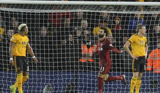 Liverpool's Mohamed Salah, centre, celebrates after scoring his side's opening goal during the English Premier League soccer match between Wolverhampton Wanderers and Liverpool at the Molineux Stadium in Wolverhampton, England, Friday, Dec. 21, 2018. (AP Photo/Rui Vieira)