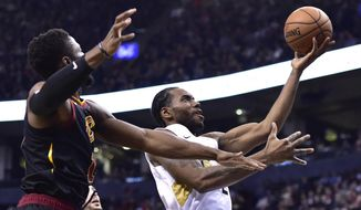 Toronto Raptors forward Kawhi Leonard, right, drives to the basket as Cleveland Cavaliers guard Rodney Hood, left, defends during second-half NBA basketball game action in Toronto, Friday, Dec. 21, 2018. (Frank Gunn/The Canadian Press via AP)