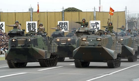 FILE - In this Oct. 14, 2018, file photo, a convoy of assault amphibious vehicles of U.S. Marine Corps, left, and Japan Self-Defense Forces, right, is driven during the Self-Defense Forces Day at Asaka Base in Asaka, north of Tokyo.  Japan's Cabinet has approved a record 5.26 trillion yen ($47 billion) defense budget as the country seeks to bolster its arms capability by increasingly buying advanced U.S. weapons. The budget plan endorsed Friday, Dec. 21 rises 1. 3 percent from the previous year, a seventh annual increase since Prime Minister Shinzo Abe took office in 2012.  (AP Photo/Eugene Hoshiko, File)
