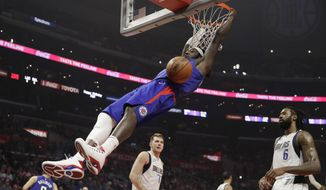 Los Angeles Clippers' Montrezl Harrell dunks in front of Dallas Mavericks' DeAndre Jordan. right, and Luka Doncic during the first half of an NBA basketball game Thursday, Dec. 20, 2018, in Los Angeles. (AP Photo/Marcio Jose Sanchez)