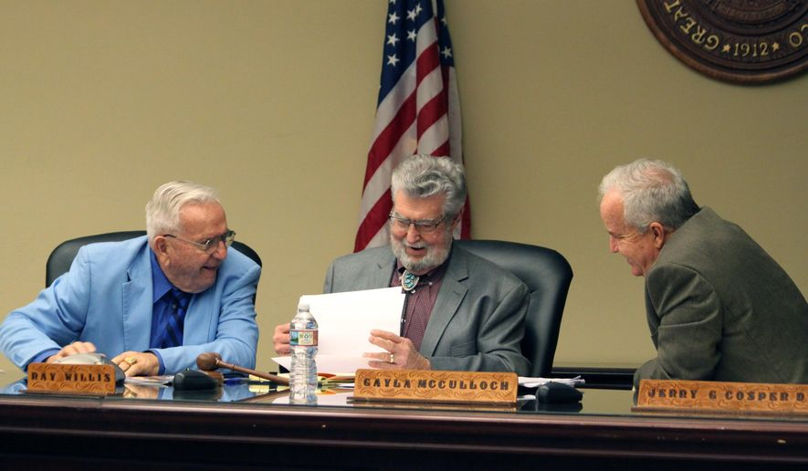 Left to right, New Mexico Racing Commission members Leonard Blach, Ray Willis and Jerry Cosper talk ahead of a special meeting in Albuquerque, N.M., on Friday, Dec. 21, 2018. Citing a pending legal petition, the commission opted to delay a decision on awarding the state's sixth and final license for a horse racetrack and casino. (AP Photo/Susan Montoya Bryan)