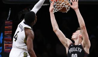 Indiana Pacers' Victor Oladipo (4) dunks against Brooklyn Nets' Rodions Kurucs (00) during the second half of an NBA basketball game, Friday, Dec. 21, 2018, in New York. (AP Photo/Noah K. Murray)
