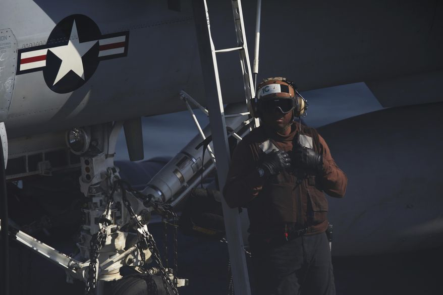 A member of the flight crew of the USS John C. Stennis aircraft carrier walks past an F/A-18 fighter jet on Friday, Dec. 21, 2018. The U.S. aircraft carrier sailed into the Persian Gulf on Friday, becoming the first since America's withdrawal from the Iran nuclear deal and breaking the longest carrier absence in the volatile region since at least the Sept. 11 terror attacks. (AP Photo/Jon Gambrell)