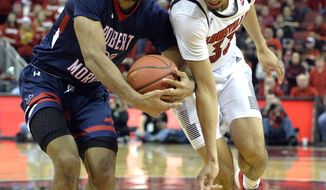 Robert Morris forward Charles Bain (20) strips the ball from Louisville forward Jordan Nwora (33) during the second half of an NCAA college basketball game in Louisville, Ky., Friday, Dec. 21, 2018. (AP Photo/Timothy D. Easley)
