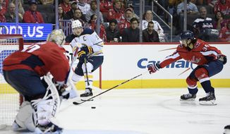 Buffalo Sabres center Jack Eichel (9) passes the puck against Washington Capitals defenseman Jonas Siegenthaler (34) and goaltender Braden Holtby (70) during the second period of an NHL hockey game, Friday, Dec. 21, 2018, in Washington. (AP Photo/Nick Wass) ** FILE **