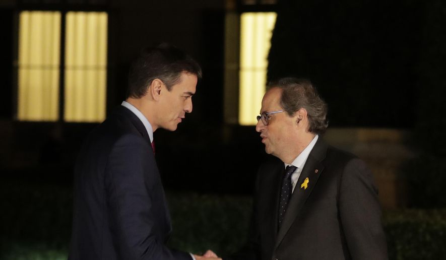 Spain's Prime Minister Pedro Sanchez, left, shakes hands with the president of the country's Catalonia region, Quim Torra before a meeting in Barcelona, Spain, Thursday, Dec. 20, 2018. Prime Minister Sanchez met with Catalonia's regional President Torra, who heads a pro-secession coalition and wants self-determination to be part of the talks. (AP Photo/Manu Fernandez)
