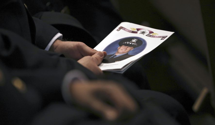 An attendee holds a program as police officers attend the funeral for Chicago police Officer Conrad Gary, Friday, Dec. 21, 2018 at St. Rita of Cascia Shrine Chapel in Chicago. Gary was one of two Chicago officers who were struck and killed by a commuter train as they were investigating a report of gunfire in the area. (Abel Uribe/Chicago Tribune via AP, Pool)
