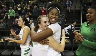 Oregon's Sabrina Ionescu, center left, and Ruthy Heard celebrate the end of an NCAA college basketball game against UC Irvine, Friday Dec. 21, 2018, in Eugene, Ore. (Chris Pietsch/The Register-Guard via AP)