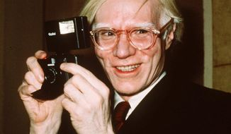 """FILE - In this 1976 file photo, pop artist Andy Warhol holds a camera in New York. A new exhibition titled, """"Andy Warhol - From A to B and Back Again,"""" is running through March 31 at the Whitney Museum of American Art in New York. (AP Photo/Richard Drew, File)"""