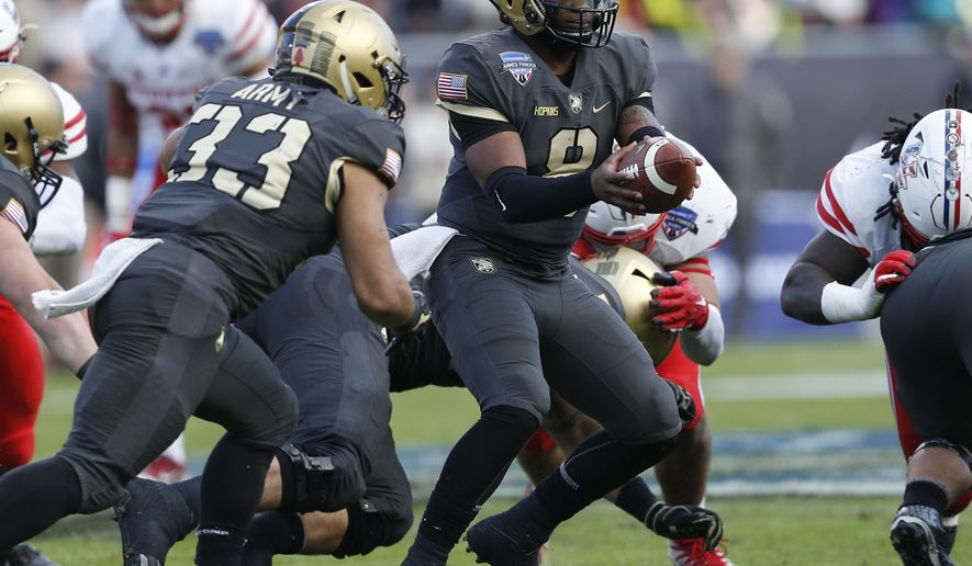 Army quarterback Kelvin Hopkins Jr. (8) prepares to hand off the ball to running back Darnell Woolfolk (33) during the first half of Armed Forces Bowl NCAA college football game against Houston, Saturday, Dec. 22, 2018, in Fort Worth, Texas. (AP Photo/Jim Cowsert)