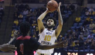 West Virginia guard Jermaine Haley (10) looks to make a pass while defended by Jacksonville State center Ty Hudson (4) during the second half of an NCAA college basketball game Saturday, Dec. 22, 2018, in Morgantown, W.Va. (AP Photo/Raymond Thompson)