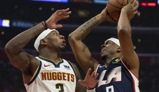 Los Angeles Clippers guard Tyrone Wallace, right, goes up to the basket under pressure as Denver Nuggets forward Torrey Craig defends him during the first half of an NBA basketball game in Los Angeles Saturday, Dec. 22, 2018. (AP Photo/Kyusung Gong)