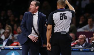 Brooklyn Nets head coach Kenny Atkinson, left, argues a call with referee Tony Brothers (25) during the second half of an NBA basketball game against the Indiana Pacers, Friday, Dec. 21, 2018, in New York. (AP Photo/Noah K. Murray)