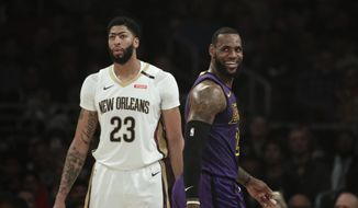 Los Angeles Lakers' LeBron James, right, smiles as he walks past New Orleans Pelicans' Anthony Davis during the first half of an NBA basketball game Friday, Dec. 21, 2018, in Los Angeles. (AP Photo/Jae C. Hong) ** FILE **