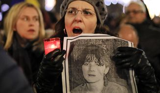 A woman held a photograph of a 1989 uprising victim while singing the national anthem along with others during a protest in Bucharest on Saturday. More than 1,000 Romanians have demanded more democracy. (Associated Press)