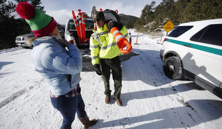 Park ranger Kevin Sturmer, right, tells Sarah Schlesinger of Boulder, Colo., that Trail Ridge Road is blocked to vehicles after a light overnight snow in Rocky Mountain National Park Saturday, Dec. 22, 2018, in Estes Park, Colo. The road was unplowed because of a partial federal shutdown that has been put in motion because of gridlock in Congress over funding for President Donald Trump's Mexican border wall.  (AP Photo/David Zalubowski)