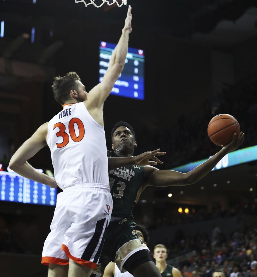 William & Mary's Nathan Knight (13) shoots around Virginia's forward Jay Huff (30) in the first half of an NCAA college basketball game,  Saturday, Dec. 22, 2018 in Charlottesville, Va. (AP Photo/Zack Wajsgras)