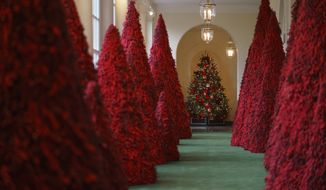 In this Nov. 26, 2018, file photo, topiary trees line the East colonnade during the 2018 Christmas preview at the White House in Washington. Melania Trump's cranberry topiary trees may have left some of her critics seeing red, but they turned out to be a hit this Christmas _ one of several new wrinkles the Trumps introduced this holiday season. (AP Photo/Carolyn Kaster, File)