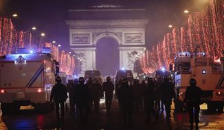 Riot police officers are seen on the Champs Elysees avenue with the Arc de Triomphe in the background, during a demonstration, in Paris Saturday, Dec. 22, 2018. France's yellow vest protesters, who have brought chaos to Paris over the past few weeks with their economic demands, demonstrated in sharply reduced numbers Saturday at the start of the Christmas and New Year holidays. (AP Photo/Kamil Zihnioglu)