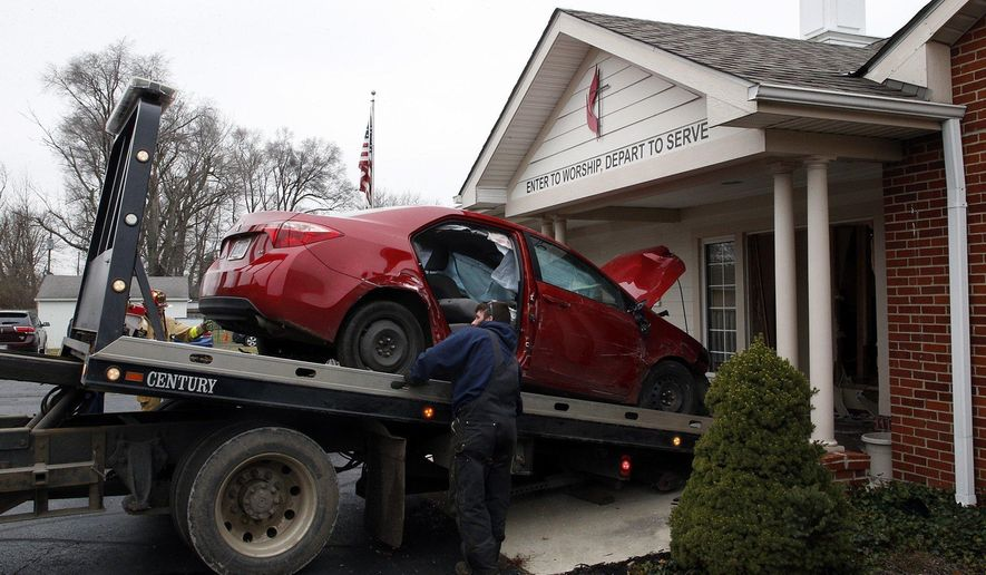 A car that crashed into the entrance of the Crossroads United Methodist Church is towed out of the doorway on Sunday, December 23, 2018 in Columbus, Ohio. A woman drove into the church during morning services, injuring several people. (Brooke LaValley/The Columbus Dispatch via AP)
