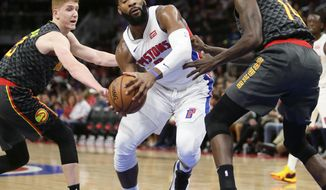 Detroit Pistons center Andre Drummond, center, drives to the basket against Atlanta Hawks guard Kevin Huerter, left, and Atlanta Hawks center Dewayne Dedmon during the first half on an NBA basketball game Sunday, Dec. 23, 2018, in Detroit. (AP Photo/Duane Burleson)