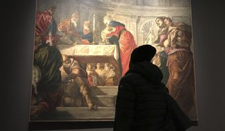 "In this Dec. 3, 2018 photo, a visitor to an exhibition of Tintoretto works looks at his ""Presentation of Jesus in the Temple"" at the Ducal Palace in Venice. After the show closes in January, it moves to the National Gallery of Art in Washington, D.C., in what would be the first-ever Tintoretto retrospective outside of Europe. (AP Photo/Frances D'Emilio)"