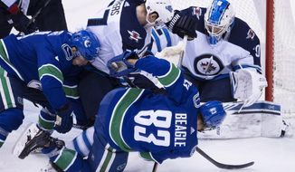 Winnipeg Jets defenseman Tyler Myers (57) stops Vancouver Canucks center Jay Beagle (83) from getting a shot on Winnipeg Jets goaltender Laurent Brossoit (30) during the second period of an NHL hockey game at Rogers Arena in Vancouver, British Columbia, Saturday, Dec. 22, 2018. (Jonathan Hayward/The Canadian Press via AP)
