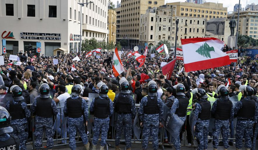 Anti-government protesters hold Lebanese flags and chant slogans as riot police stand guard in front of the government building, in central Beirut, Lebanon, Sunday, Dec. 23, 2018. Hundreds of Lebanese protested against deteriorating economic conditions as politicians are deadlocked over forming a new government. (AP Photo/Bilal Hussein)