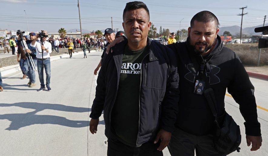 """In this Dec. 11, 2018 file photo, Irineo Mujica, activist with """"Pueblo Sin Fronteras,"""" or People Without Borders, center, is accompanied by an unidentified man as he enters the U.S. consulate during a demonstration by Central American migrants in Tijuana, Mexico.  The activist group that escorted thousands of Central Americans to the U.S. border is under fire from allies and some of the migrants themselves. They say the organization downplayed the dangers of the trek and misled them about how long they would have to wait around to apply for asylum. Pueblo Sin Fronteras, or People Without Borders, is defending itself, saying the migrants made their own decision to press on toward the United States. (AP Photo/Moises Castillo)"""