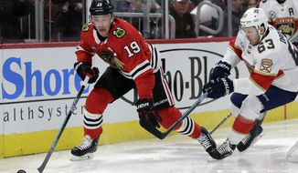 Chicago Blackhawks center Jonathan Toews, left, controls the puck against Florida Panthers right wing Evgenii Dadonov during the first period of an NHL hockey game Sunday, Dec. 23, 2018, in Chicago. (AP Photo/Nam Y. Huh)