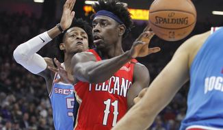 New Orleans Pelicans guard Jrue Holiday (11) passes the ball against Sacramento Kings guard De'Aaron Fox (5) during the first half of an NBA basketball game in Sacramento, Calif., Sunday, Dec. 23, 2018. (AP Photo/Steve Yeater)