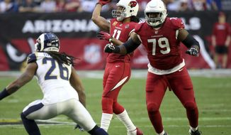 Arizona Cardinals wide receiver Larry Fitzgerald (11) throws a touchdown pass against the Los Angeles Rams during the first half of an NFL football game, Sunday, Dec. 23, 2018, in Glendale, Ariz. (AP Photo/Ross D. Franklin)