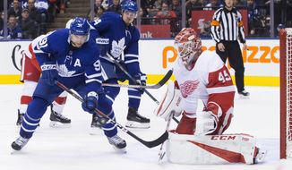 Toronto Maple Leafs John Tavares, left, attempts to tip the puck past Detroit Red Wings goaltender Jonathan Bernier as teammate Auston Matthews looks on during second period NHL hockey action in Toronto, on Sunday, Dec. 23, 2018. (Chris Young/The Canadian Press via AP)