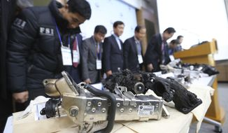 South Korean Transport Ministry officials and members of investigative panel on BMW engine bow during a press conference as damaged gears of a BMW which engine had caught fire are displayed at the government complex in Seoul, Monday, Dec. 24, 2018. South Korea says it will fine BMW 11.2 billion won ($9.9 million) and file a criminal complaint against the company with state prosecutors over an allegedly botched response to dozens of engine fires reported in the country. (AP Photo/Ahn Young-joon)